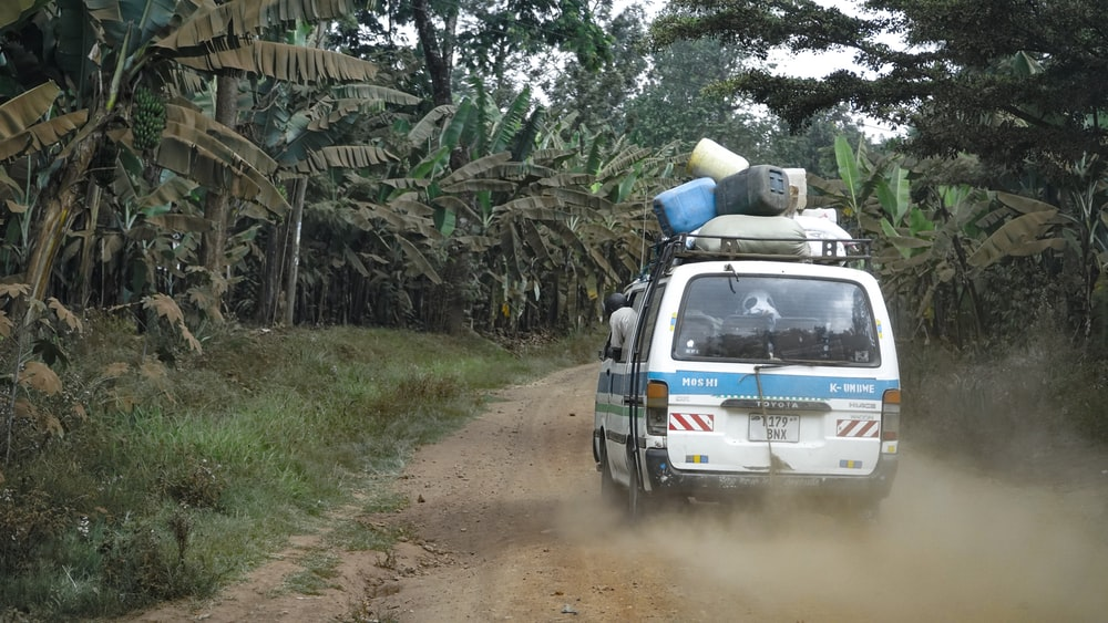 assorted-color plastic containers on top of white van travelling on brown dirt road near green banana trees during daytime