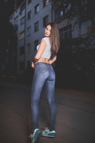 woman in blue jeans and white top in the middle of the road