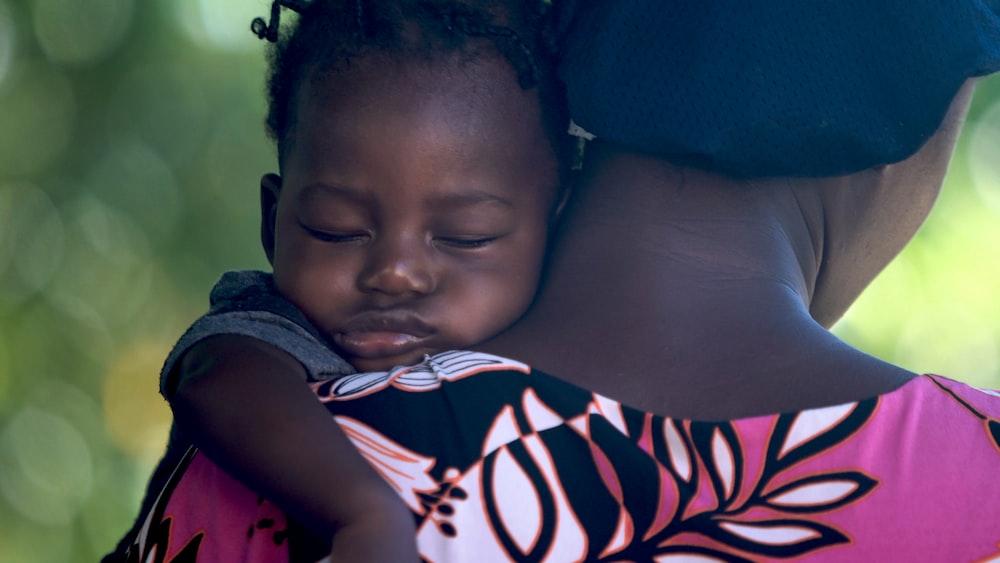 girls sleeping on mother's shoulder