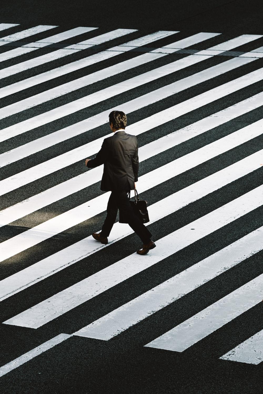 man in black formal suit jacket and pants carrying black bag while walking on pedestrian lane during daytime