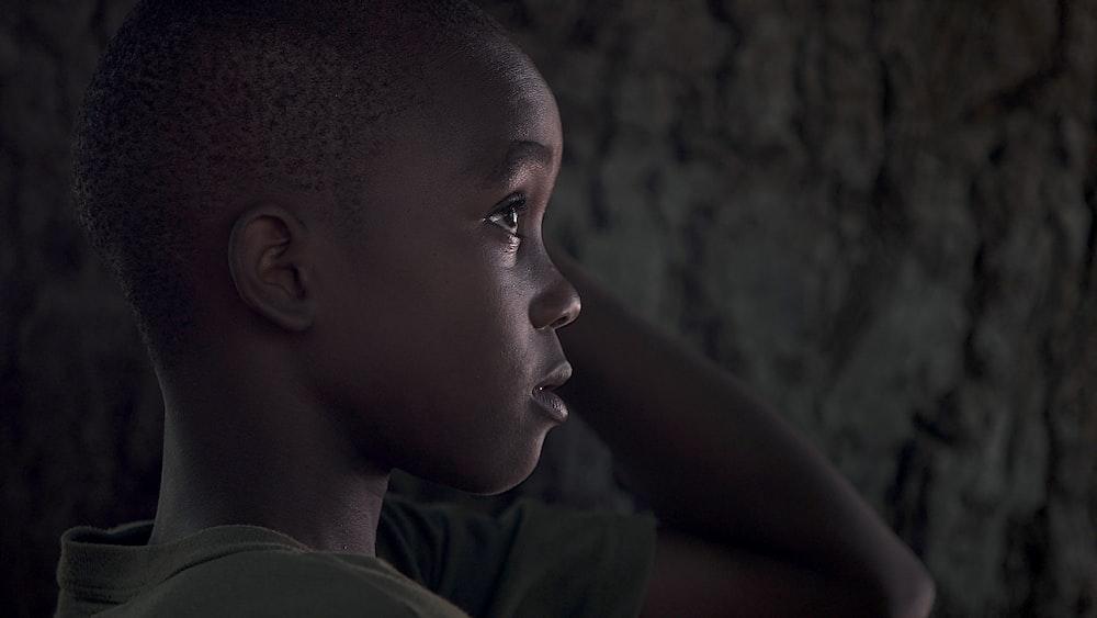 boy wearing grey shirt while touching his head