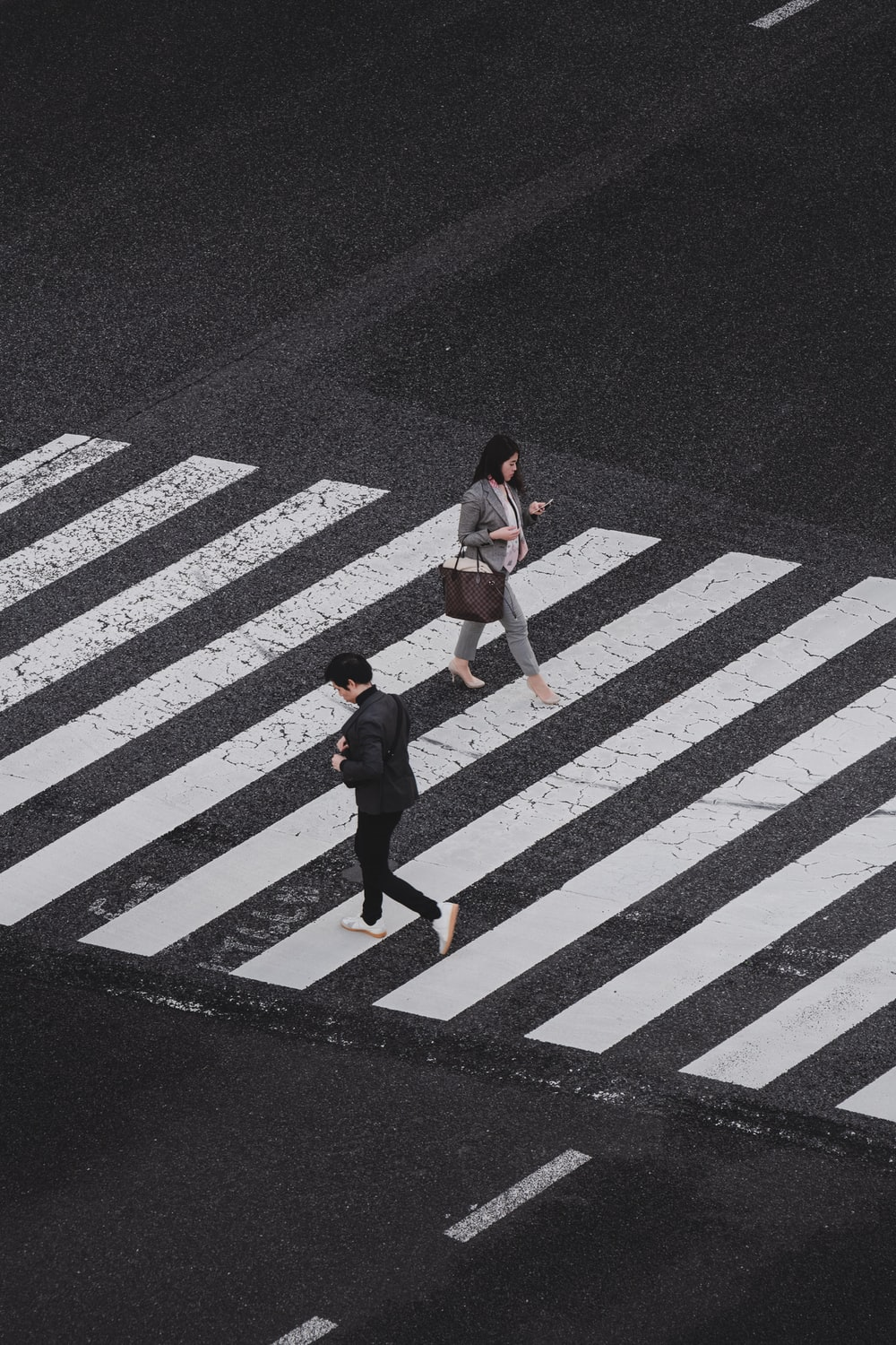 aerial photography of man and woman walking on pedestrian lane during daytime