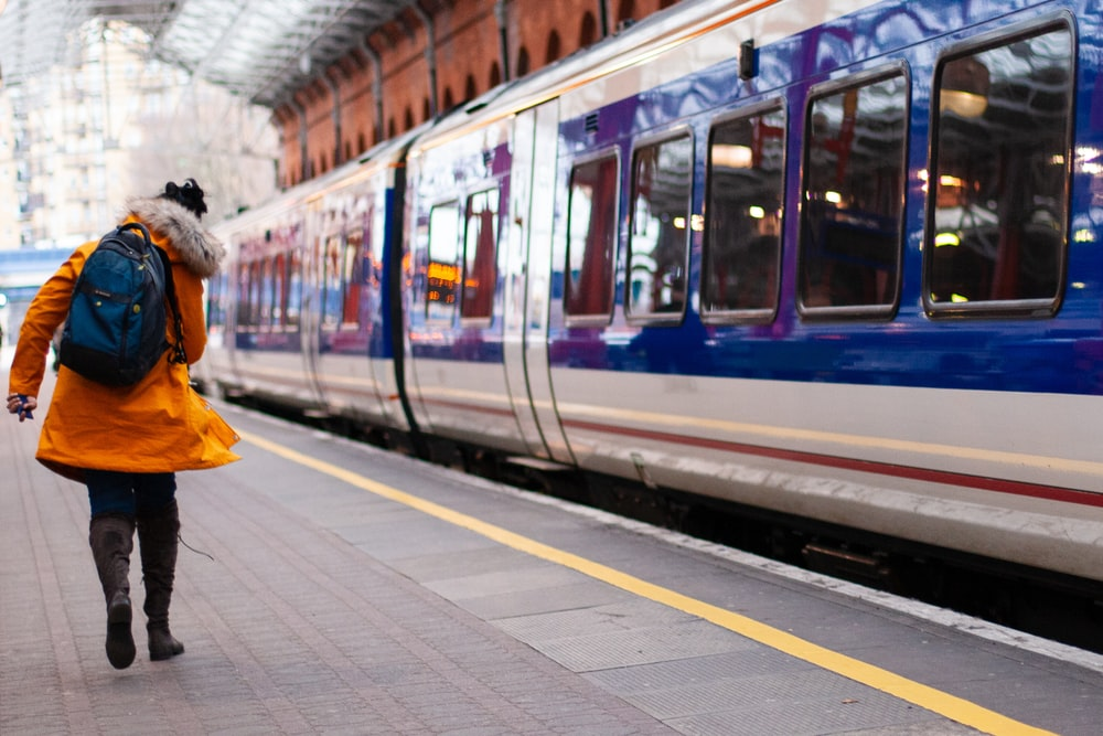 woman in orange coat walking beside train at the station