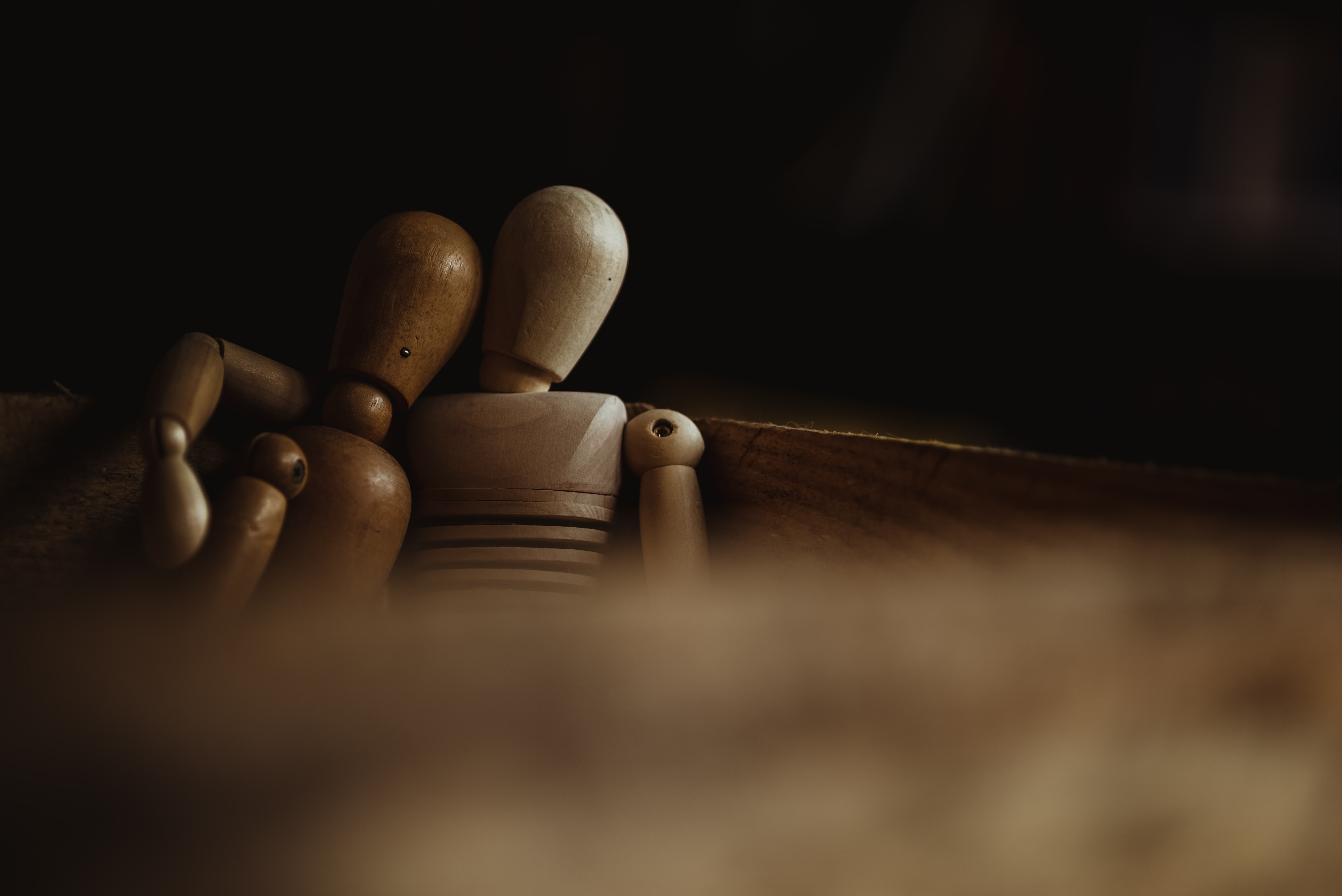 close-up photo of two wooden mannequins sitting on bench