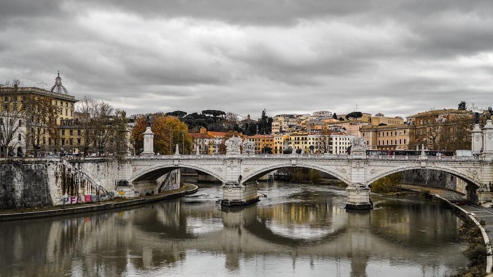 white bridge across river near city buildings during daytime