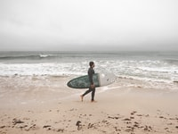 man holding surf board on seashore during daytime