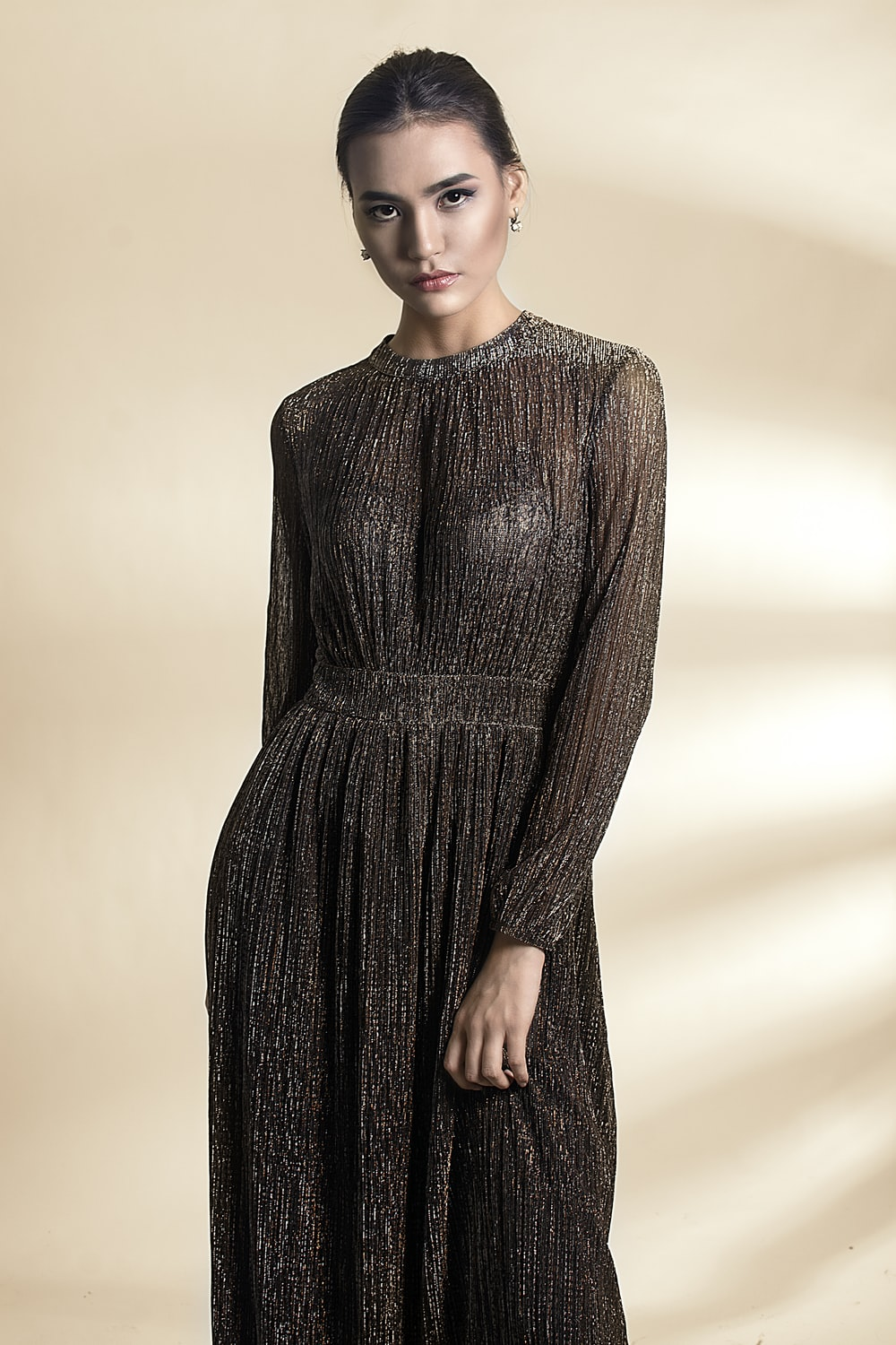 woman in black long-sleeved glittered dress posing beside wall