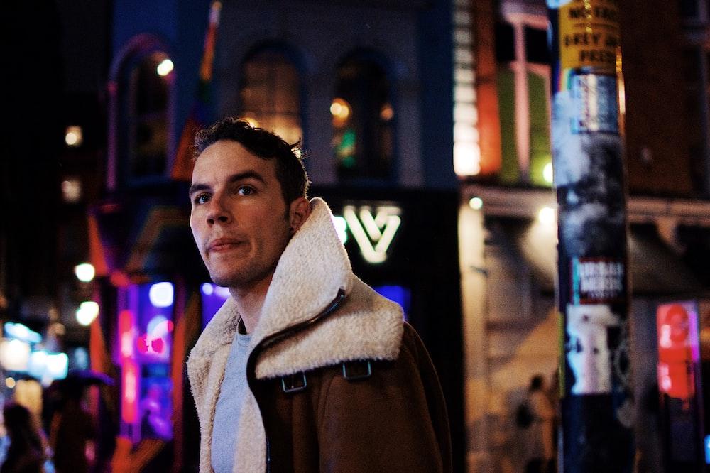 man in brown jacket standing beside building