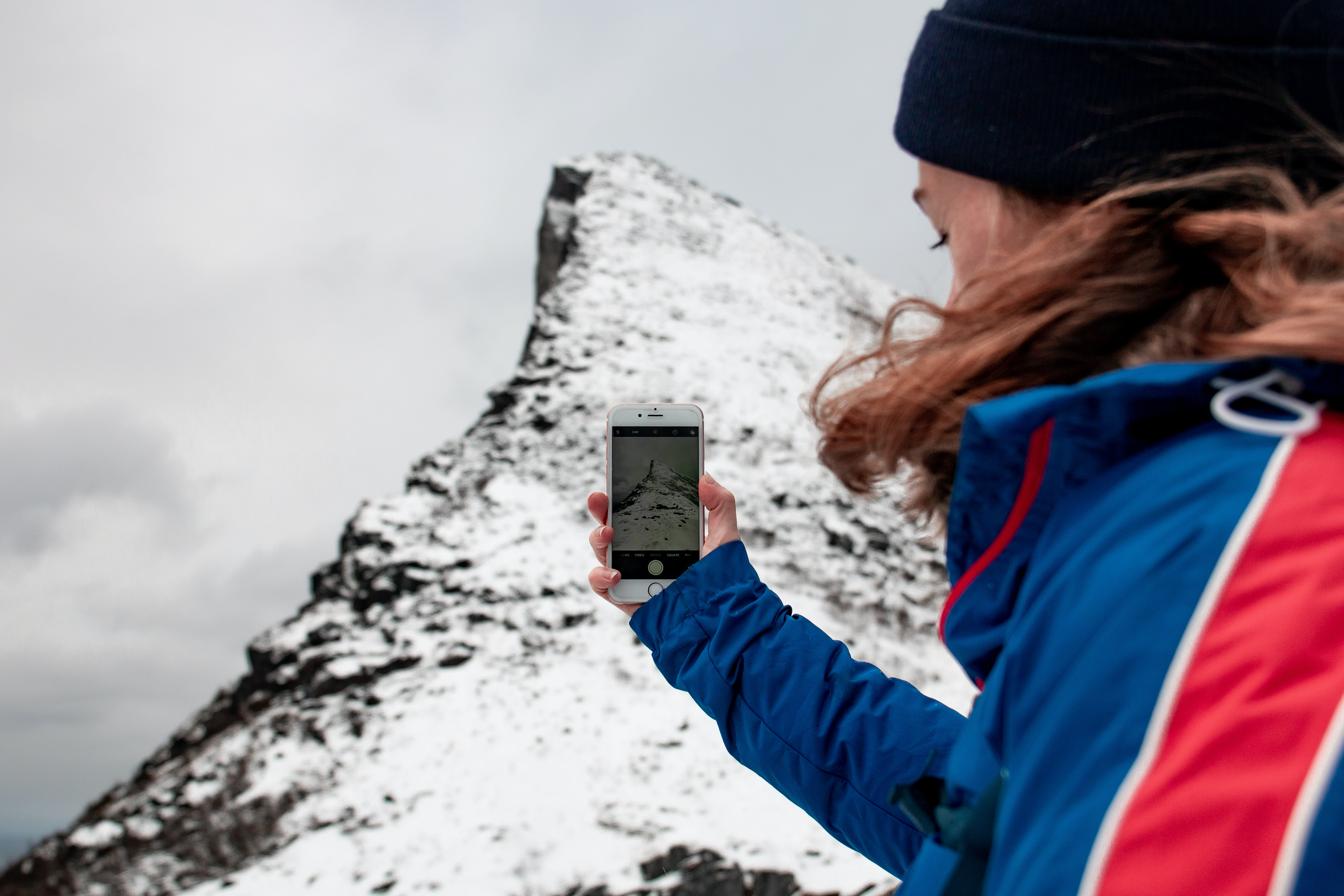 woman taking picture on mountain