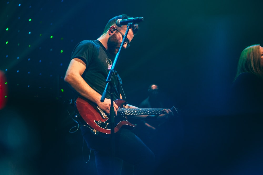 man playing with guitar performing on stage