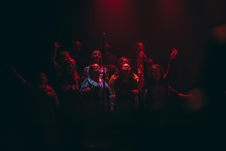 group of person singing on dark ara