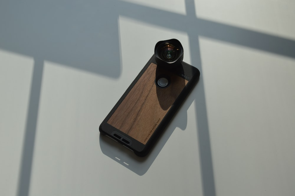 brown and black smartphone with lens
