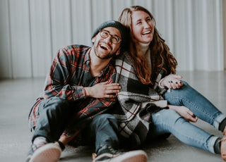smiling woman and man sitting on floor