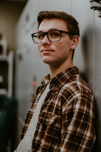 man wearing eyeglasses while leaning on wall