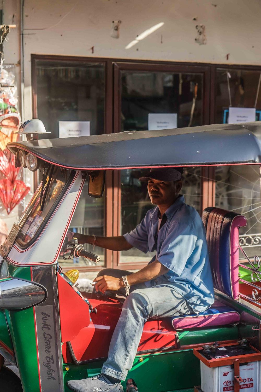 man riding autorickshaw beside concrete building