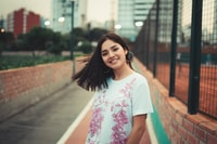 selective focus photography of smiling woman wearing white and pink floral t-shirt