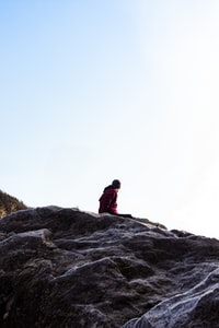 person sitting on gray rocky hill