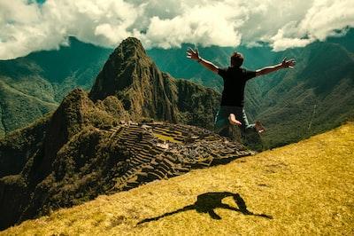 man jumping in green open field peru zoom background