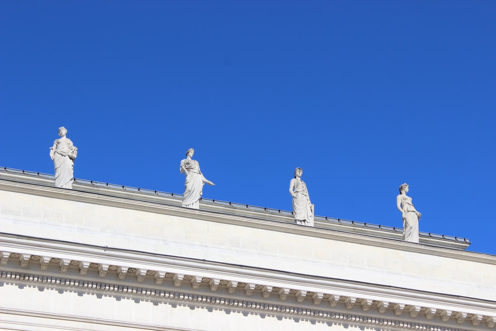 four white concrete statue under clear blue sky