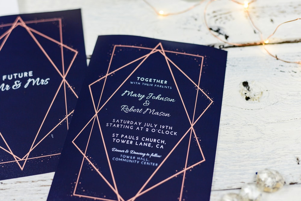 wedding invitation card on brown wooden surface