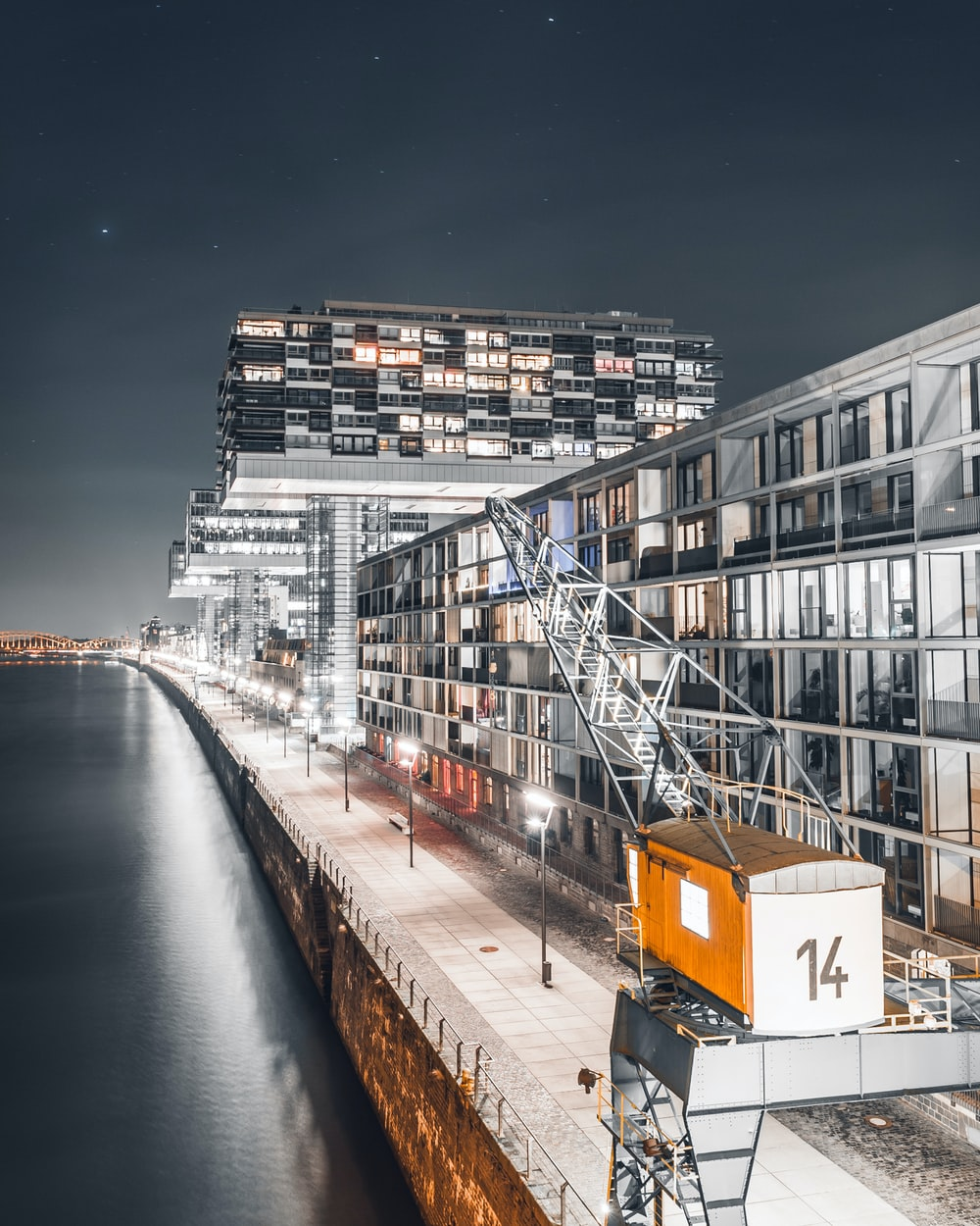 gray glass building beside body of water during night time