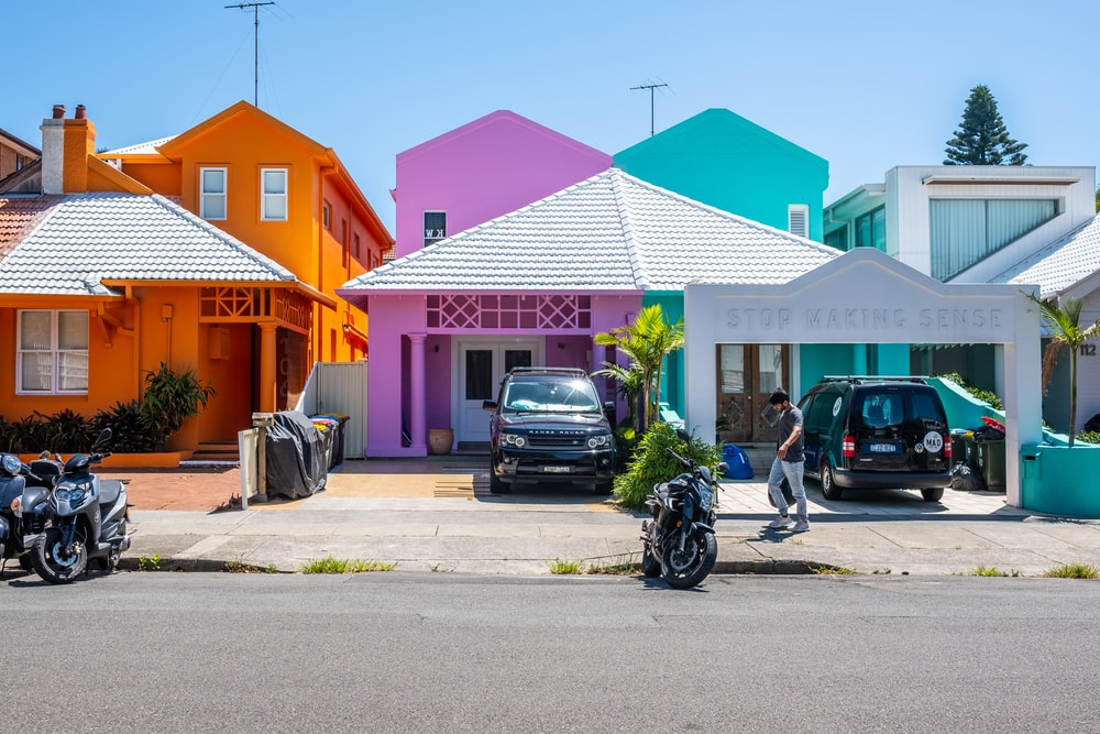 black Land Rover Freelander parked in front of pink house during daytime