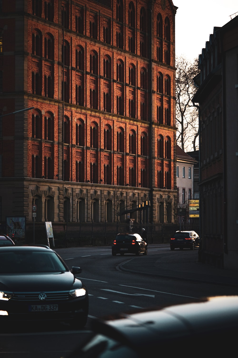 cars traveling on street by the tall brown building