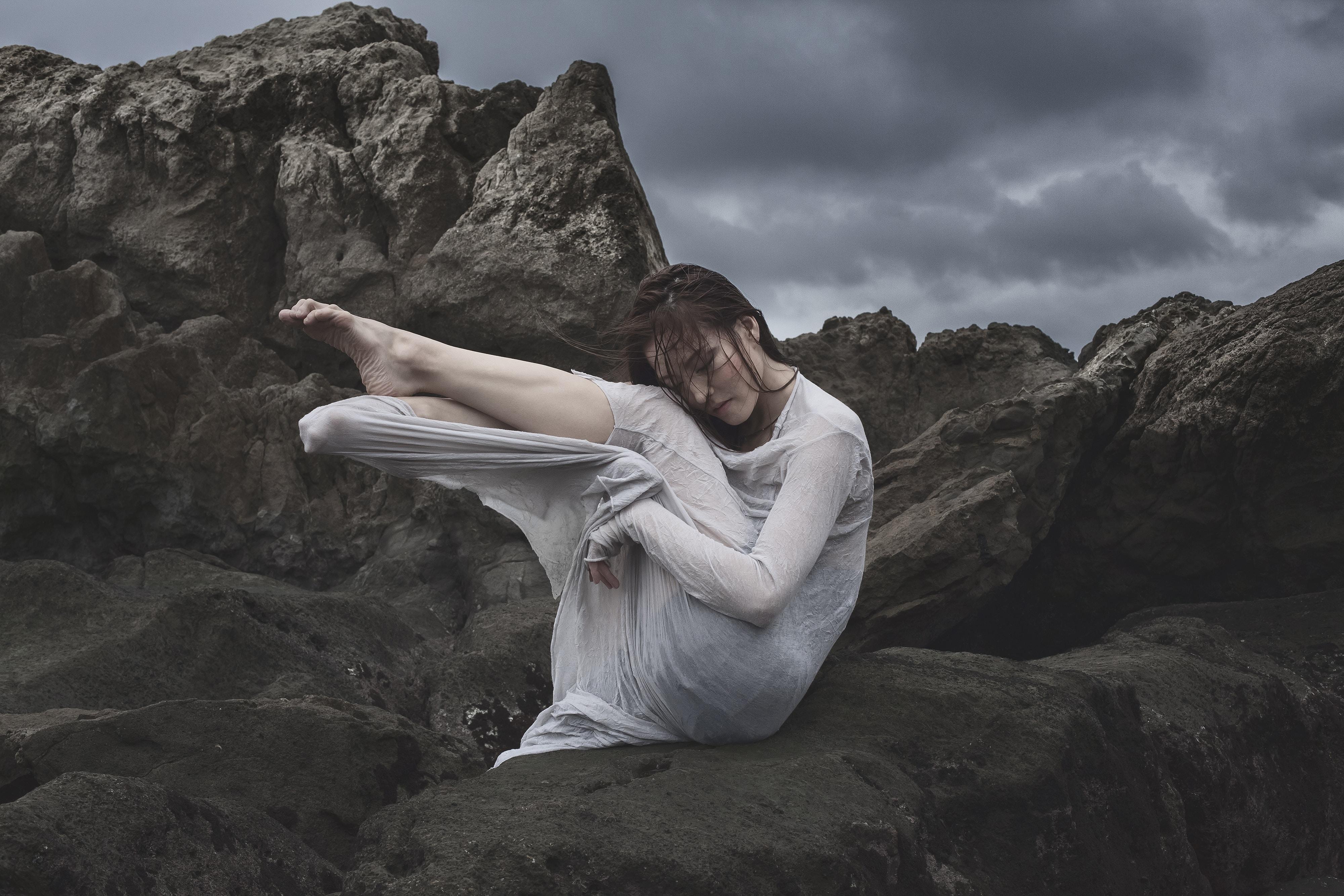 woman sitting on black stone