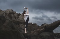 woman in white top standing on gray rock