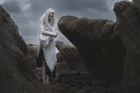 woman in white headscarf standing near rocks during daytime