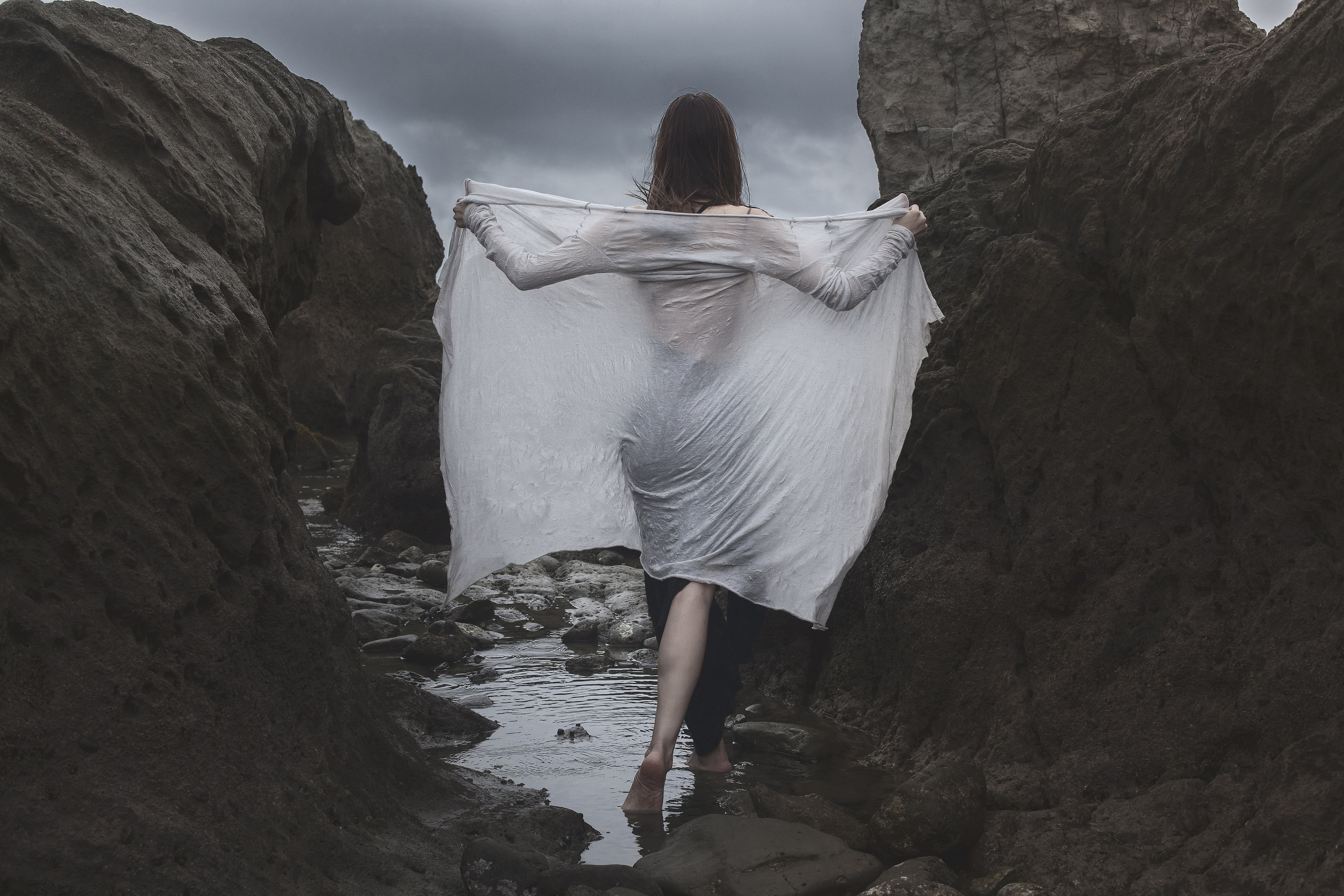 woman standing and covering white towel between rock formation