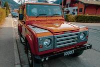 red Land Rover Defender parked on roadside during daytime