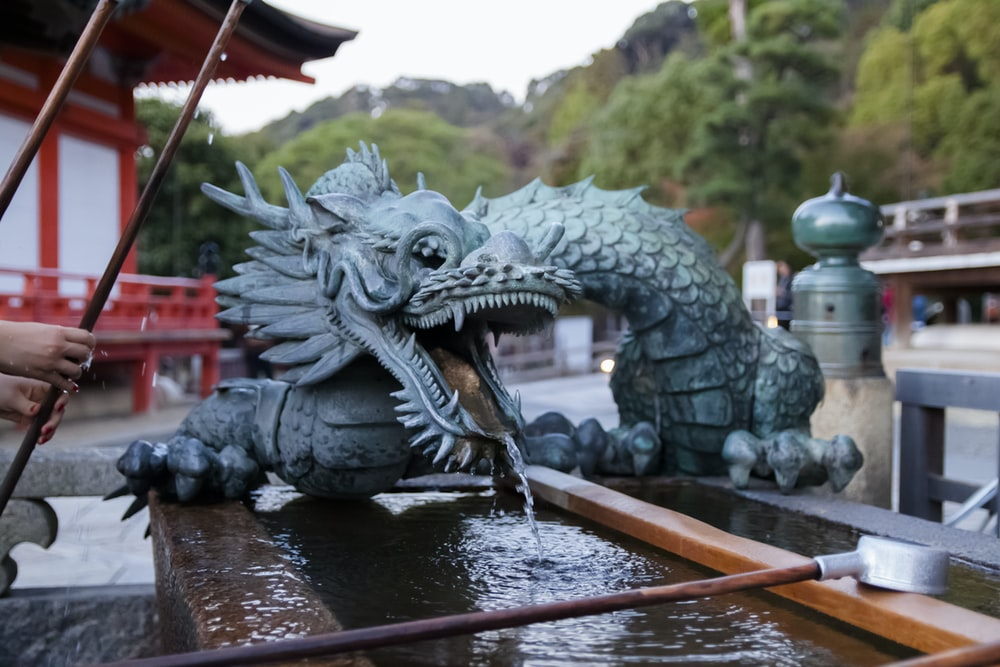 selective focus photography of blue dragon mini water fountain