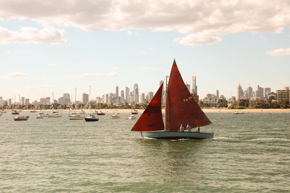 red and white sailboat at middle of sea
