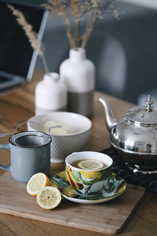 gray teapot beside mug filled with tea and lemon on top of table