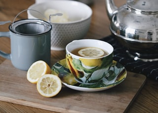gray teapot beside mug filled with tea and lemon on top of table