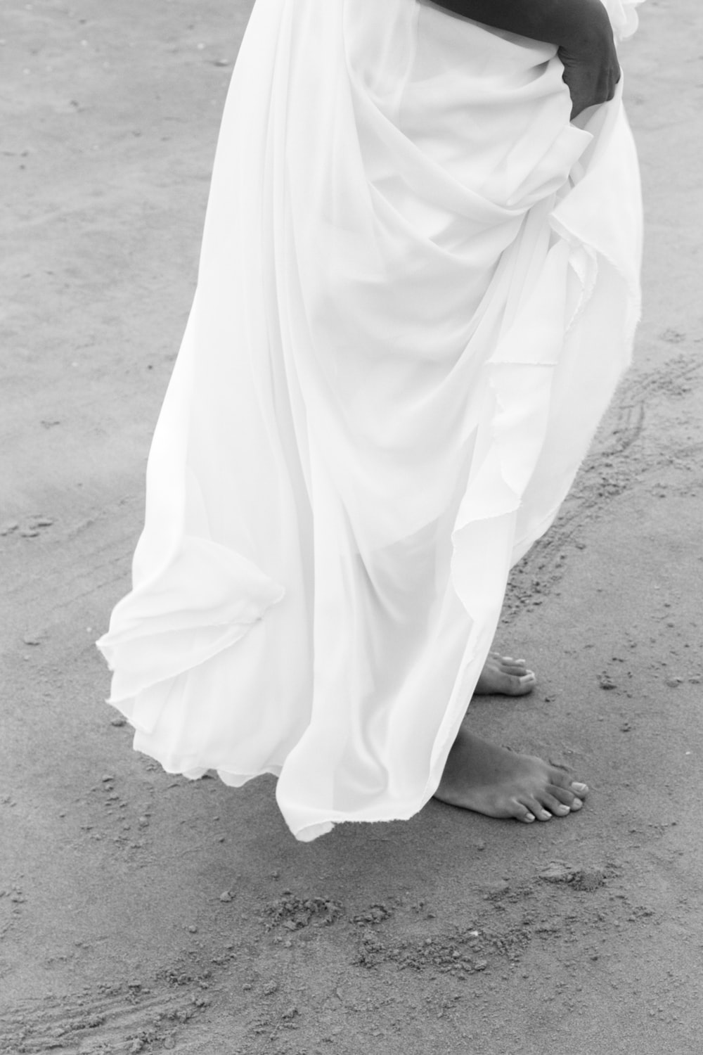 barefooted woman in long skirt during daytime greyscale photography