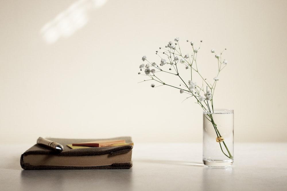 white petaled flower in glass vase beside book