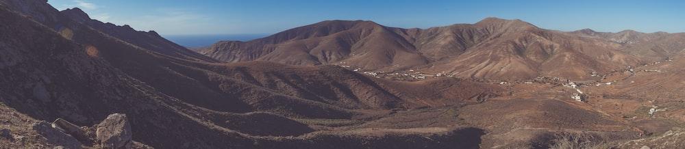 brown open field mountain range under blue sky