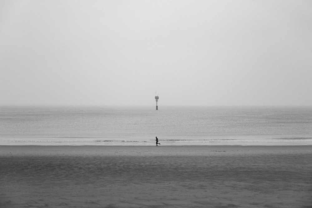 grayscale photo of person running on seashore