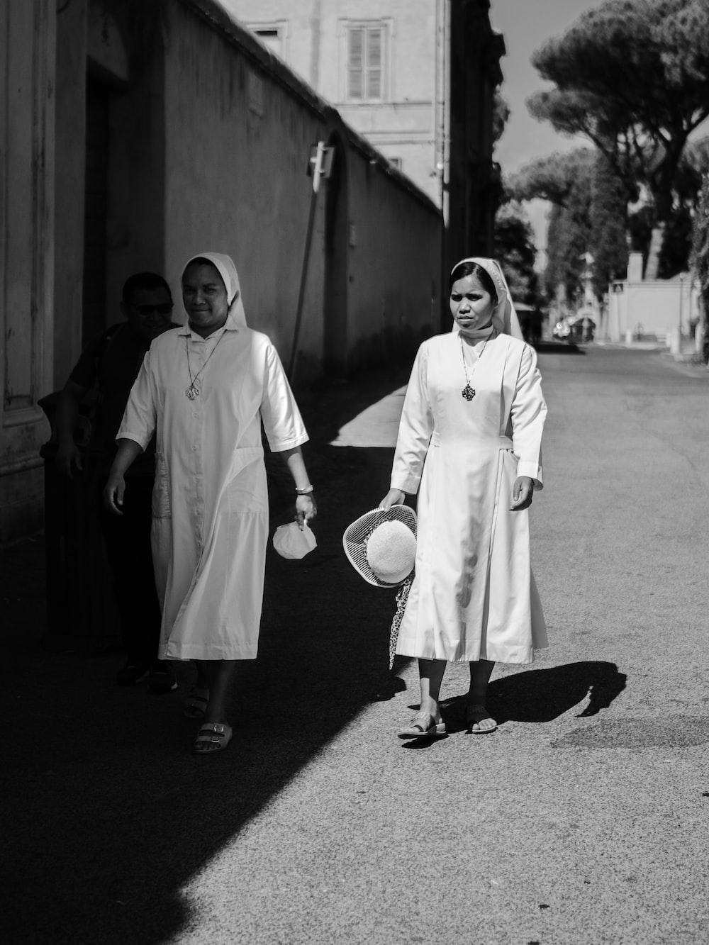 two nun walking beside house