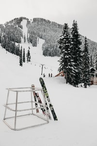 2 pairs of ski on metal stand on mountain slope