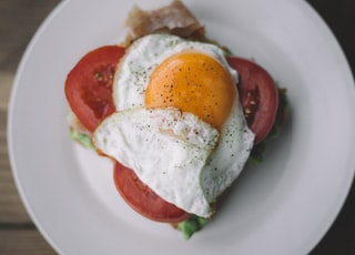 fried egg with black pepper and sliced tomatoes