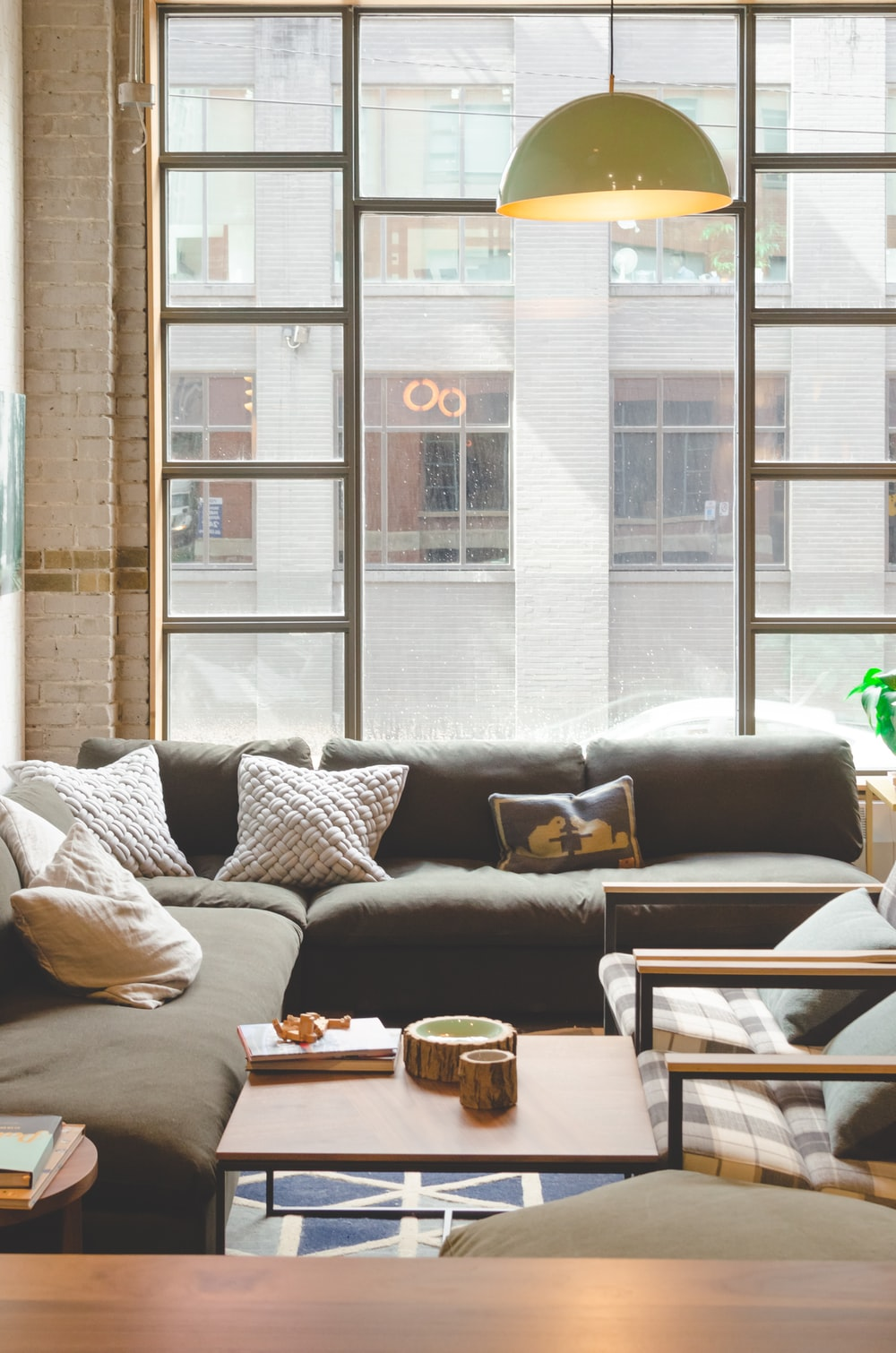 throw pillows on sectional sofa inside building with pendant lamp turned on