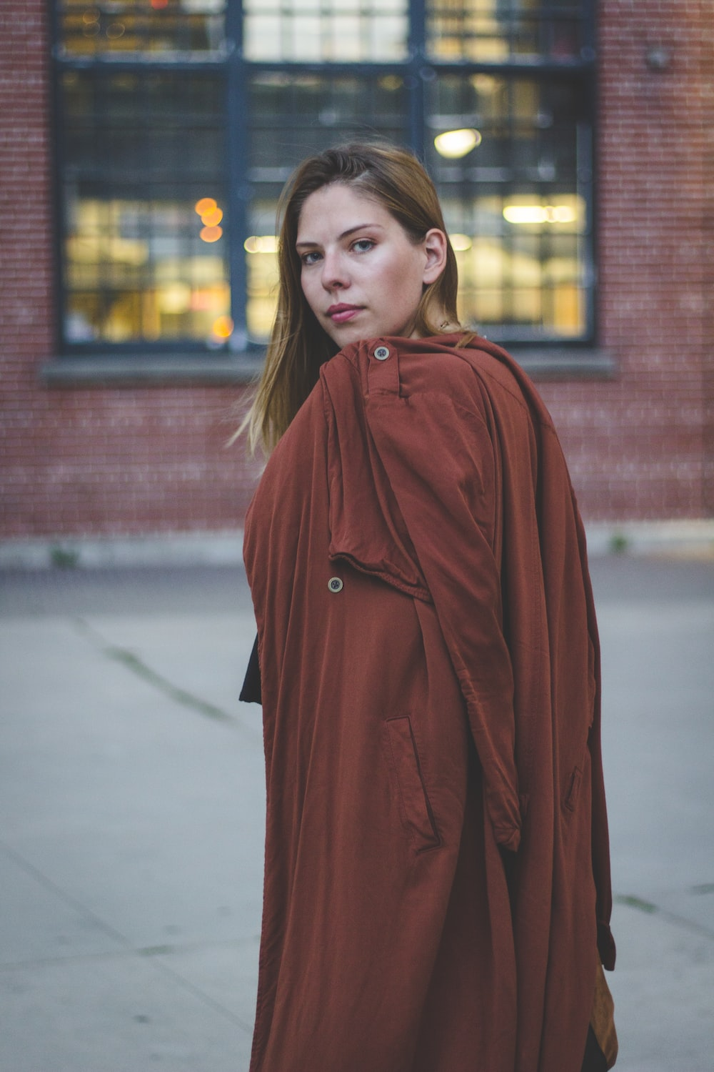 woman standing and holding red coat