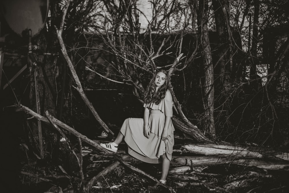 grayscale photo of woman in dress standing on tree branch