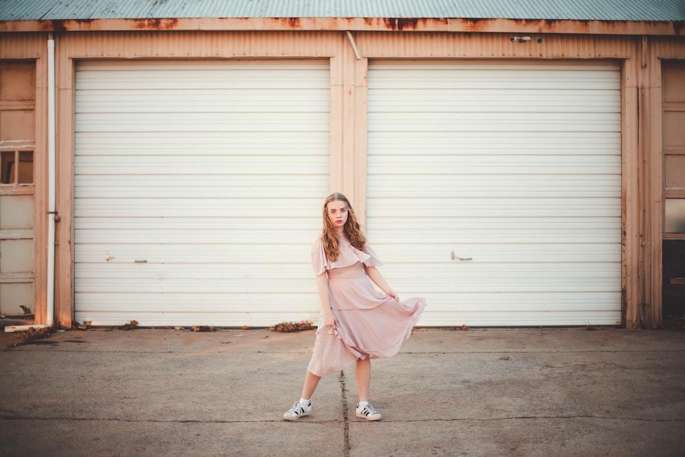 woman wearing dress standing in front of garage doors