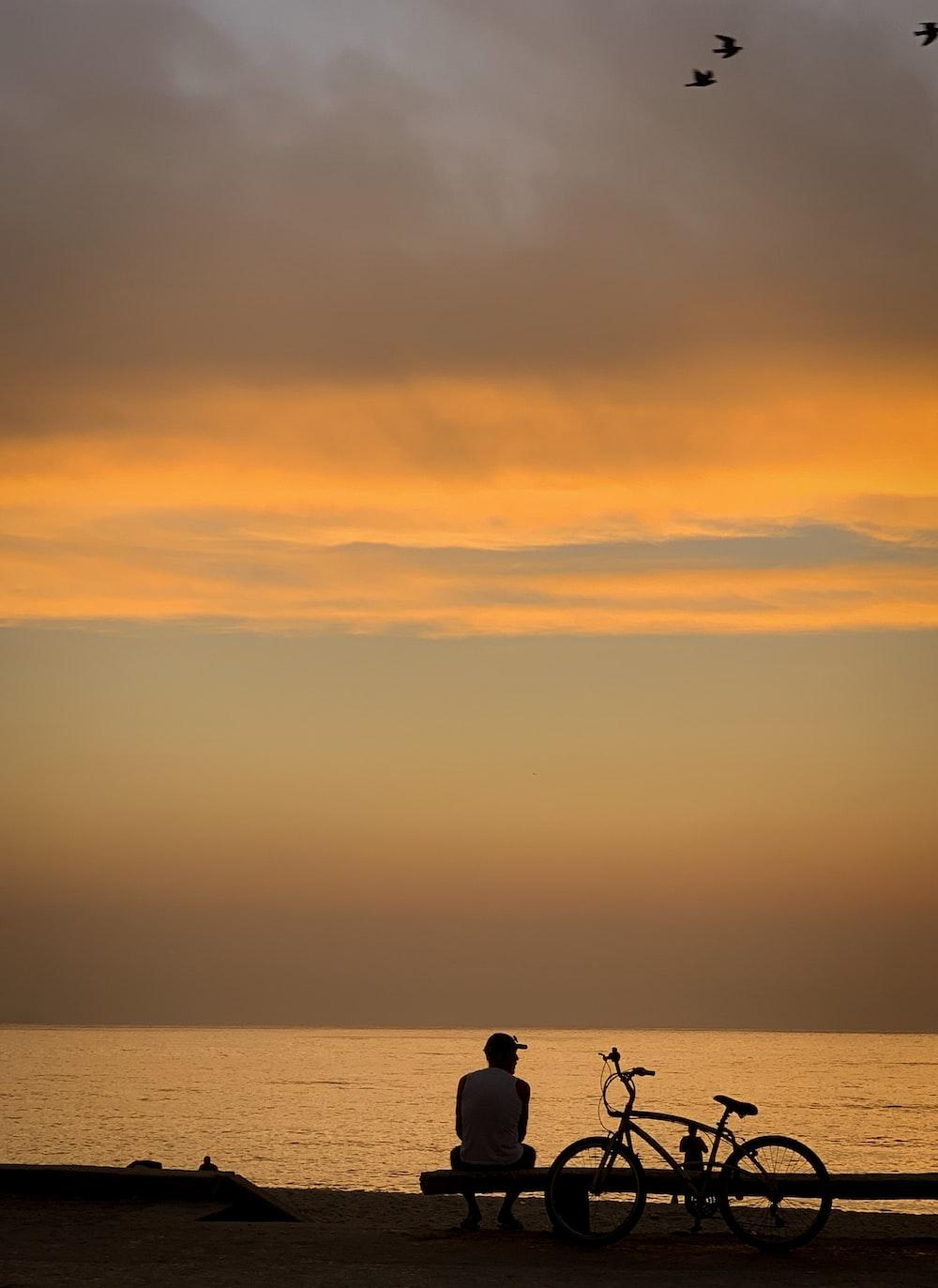 man sitting near bike at sunset