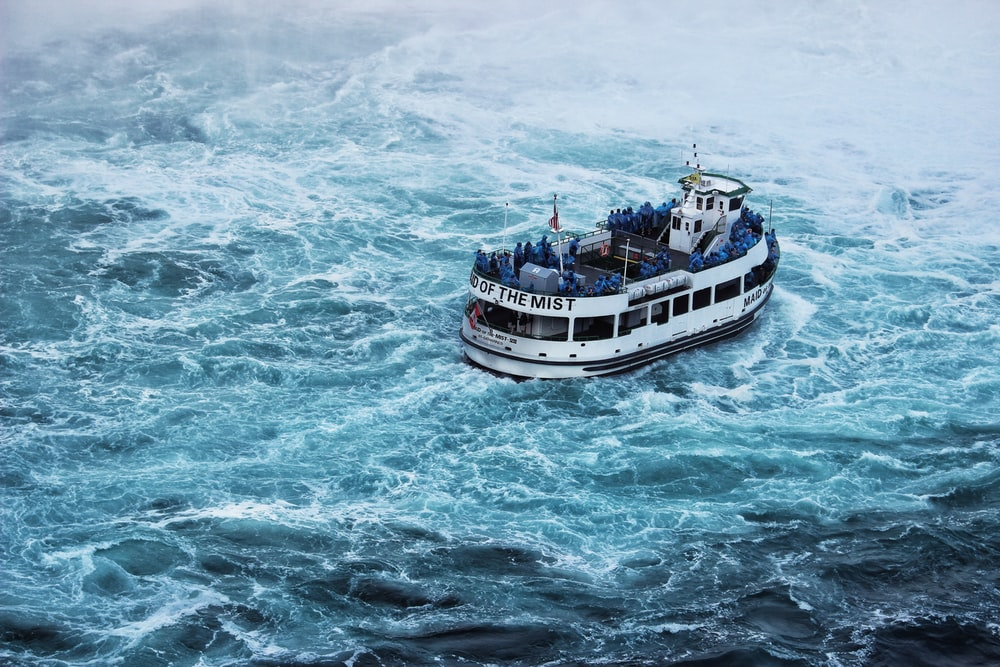 grey ferry sailing on blue turbulent waters