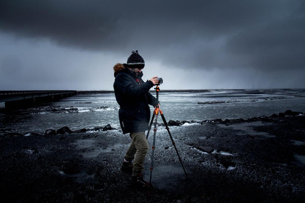 man taking photo using tripod at sea